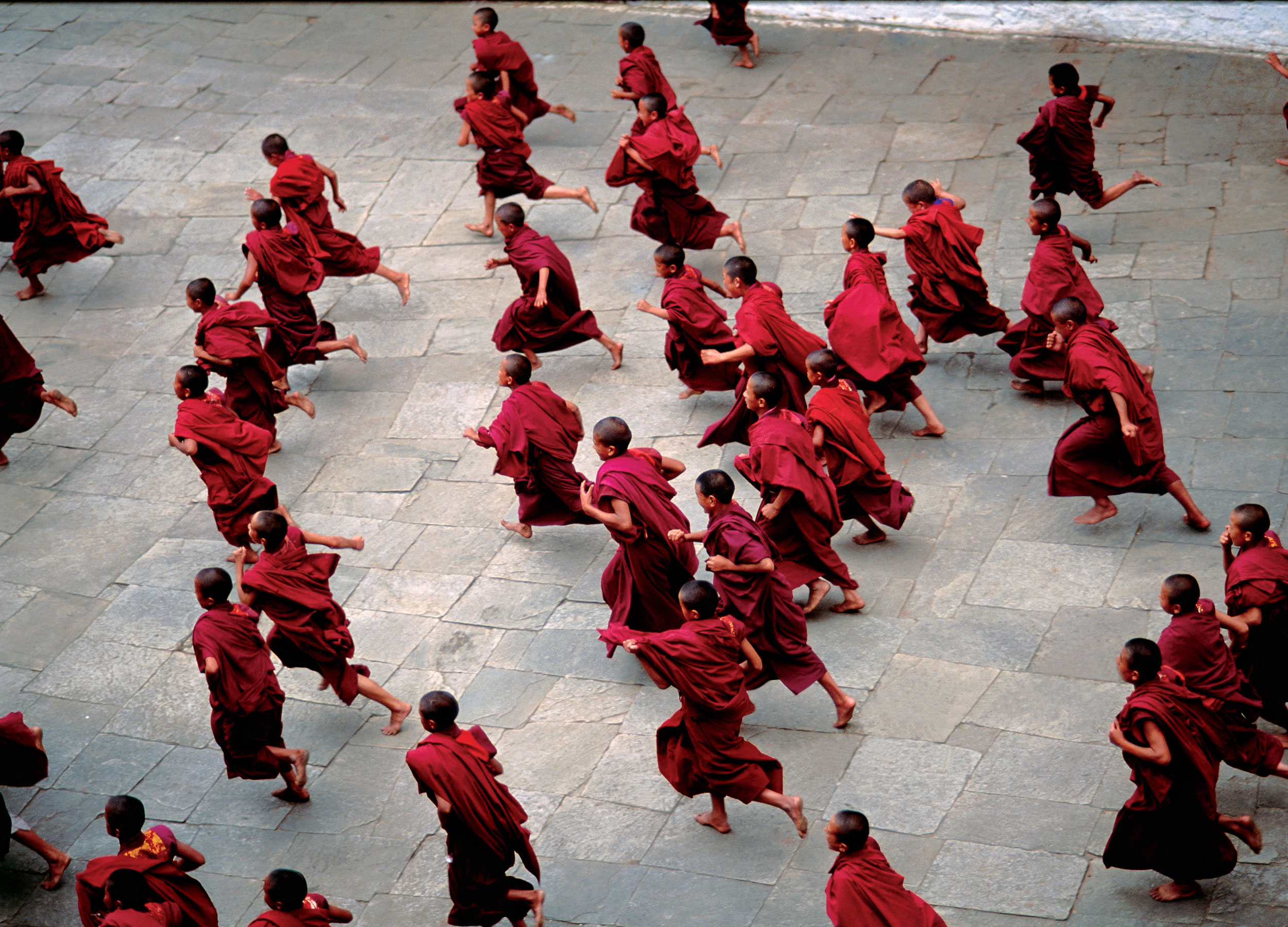 A group of red-robed monks running down a stone pavement