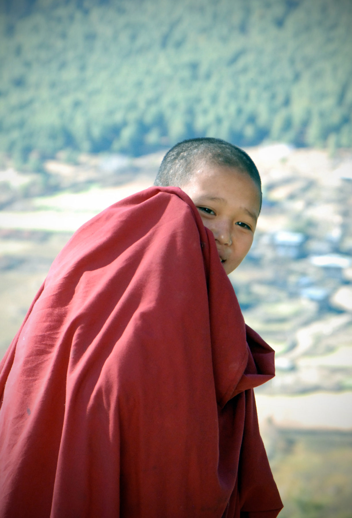 Young boy monk smiling shyly from behind his robe shielding his face i Bhutan
