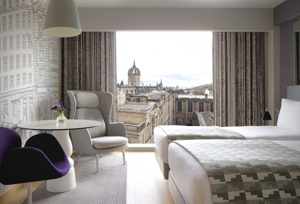 A twin bedded Superior Room at G&V Hotel in a grey palette with a purple chair looking out onto Edinburh