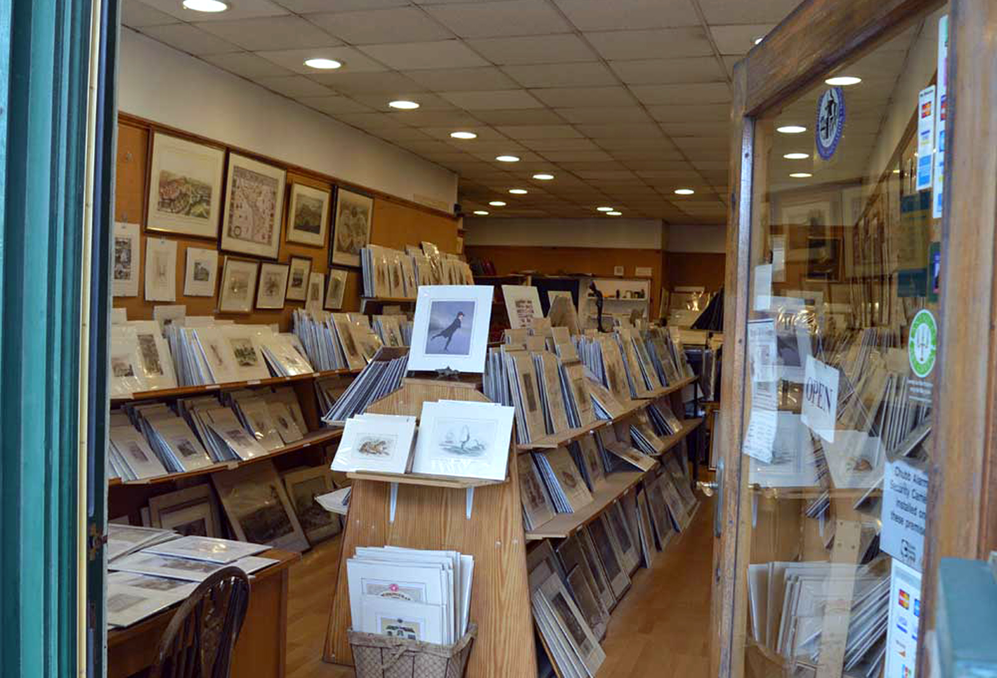 View into Royal Mile Gallery, Edinburgh of wooden shelves carrying vintage maps and prints, .