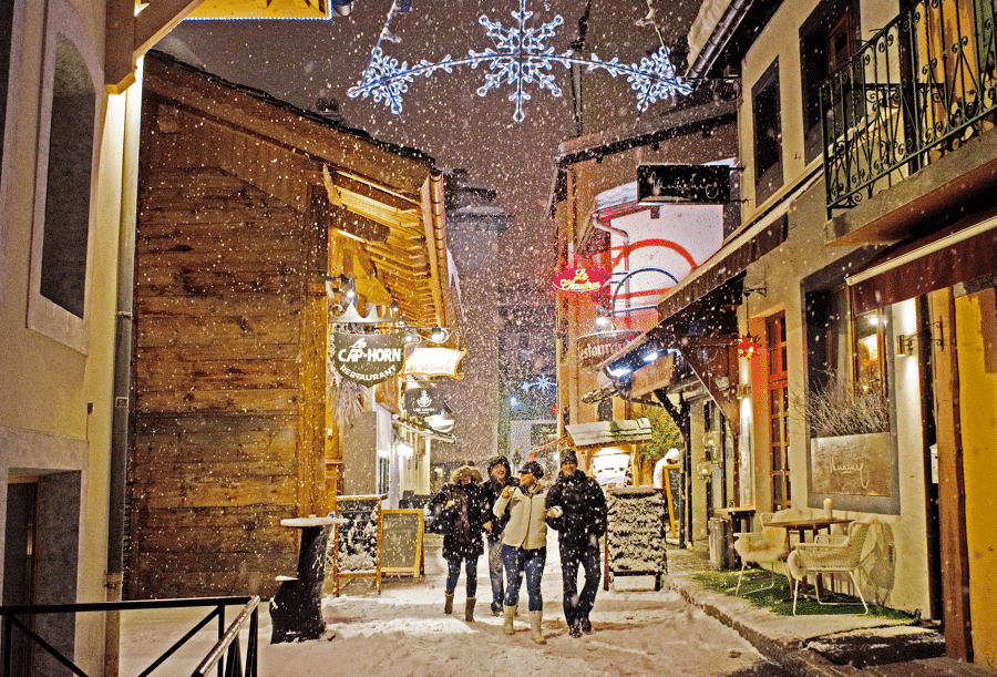 Group walking through the streets of Chamonix with snow falling