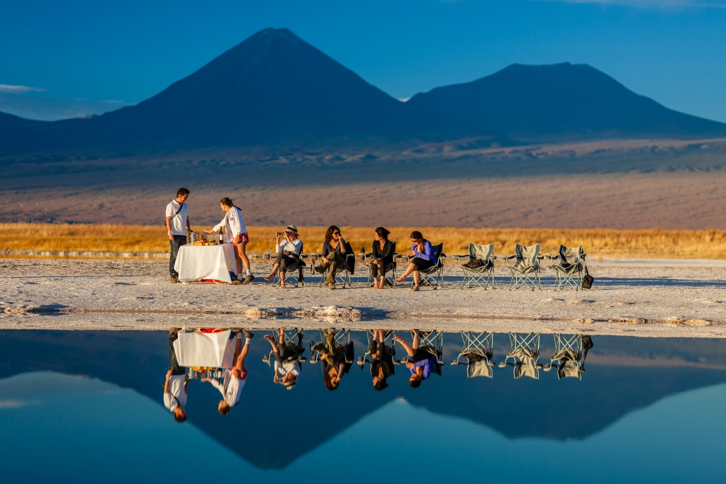 Group of women sitting by a salt lake and all being reflected into the water