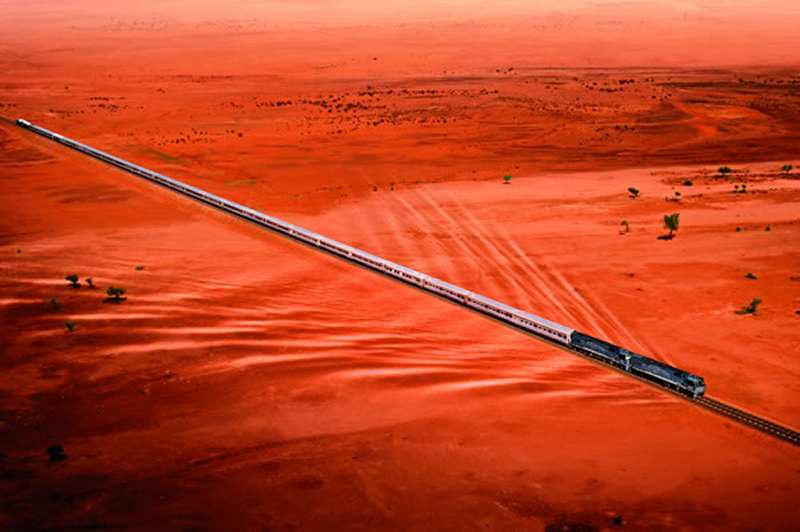 Aerial view of a train crossing a red desert on a poker straight track, Australia