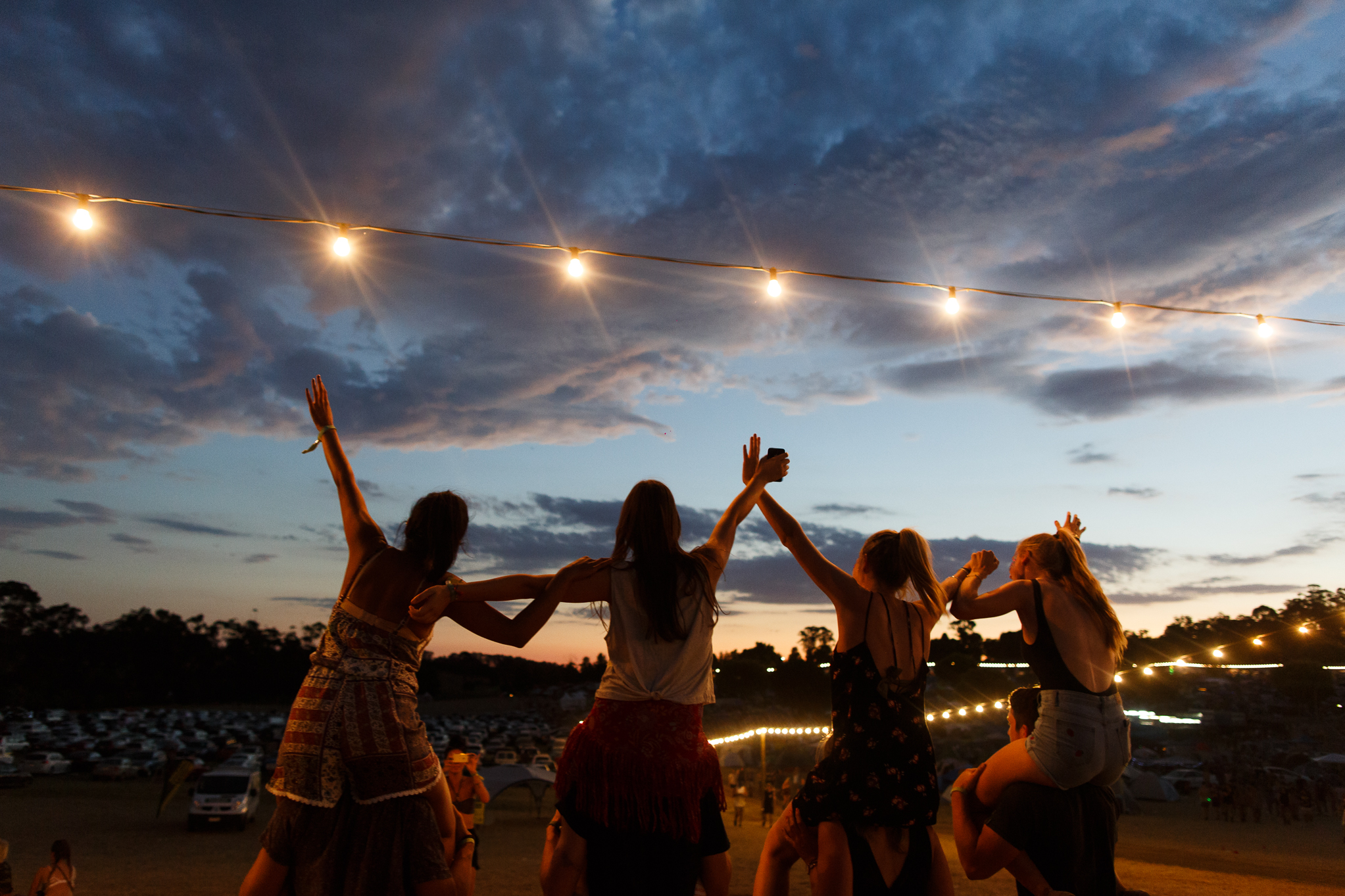 Four girls piggy back dancing with arms in the air at Beyond the Valley Festival, Australia