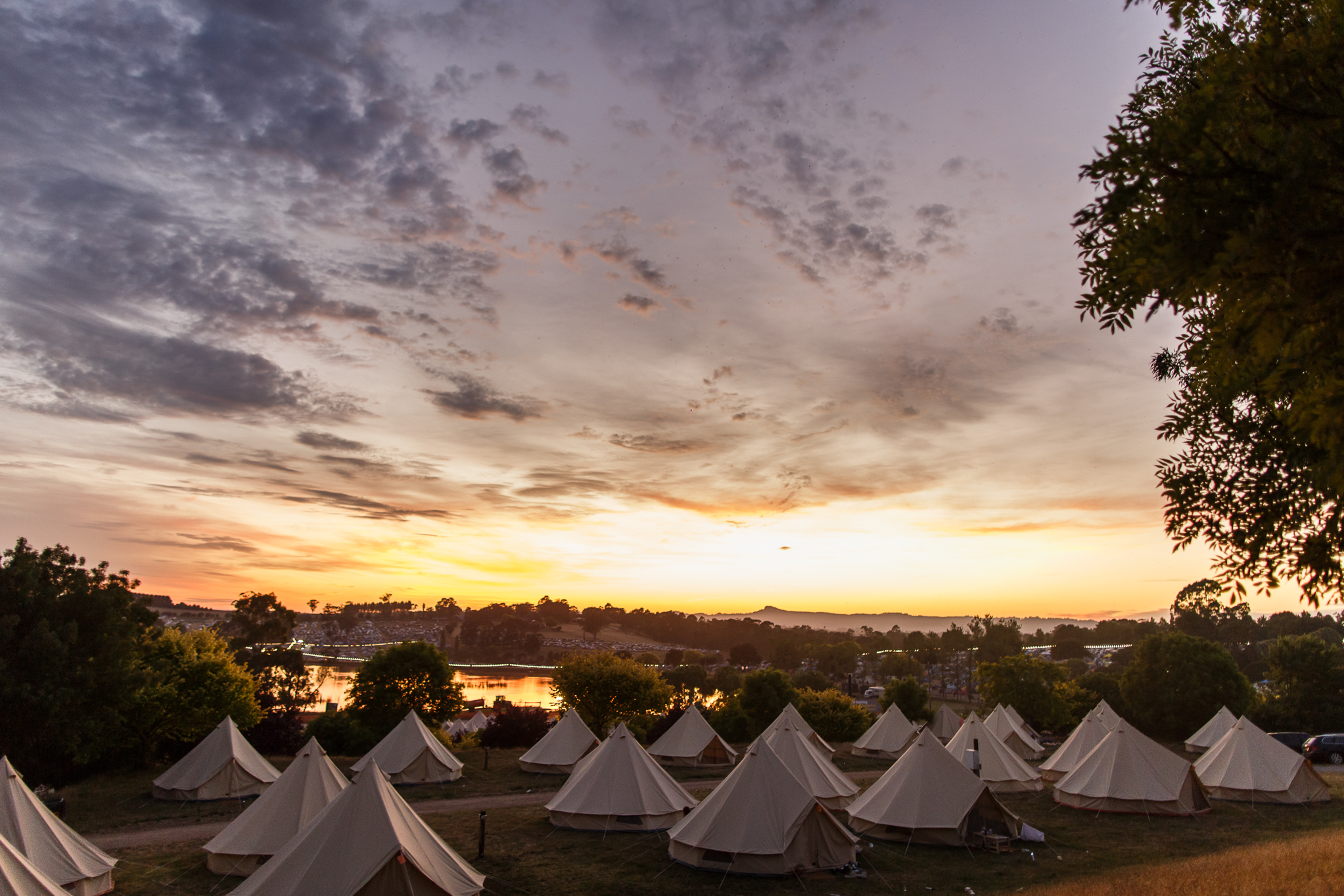 Rows of white tents at sunset overlooking the festival