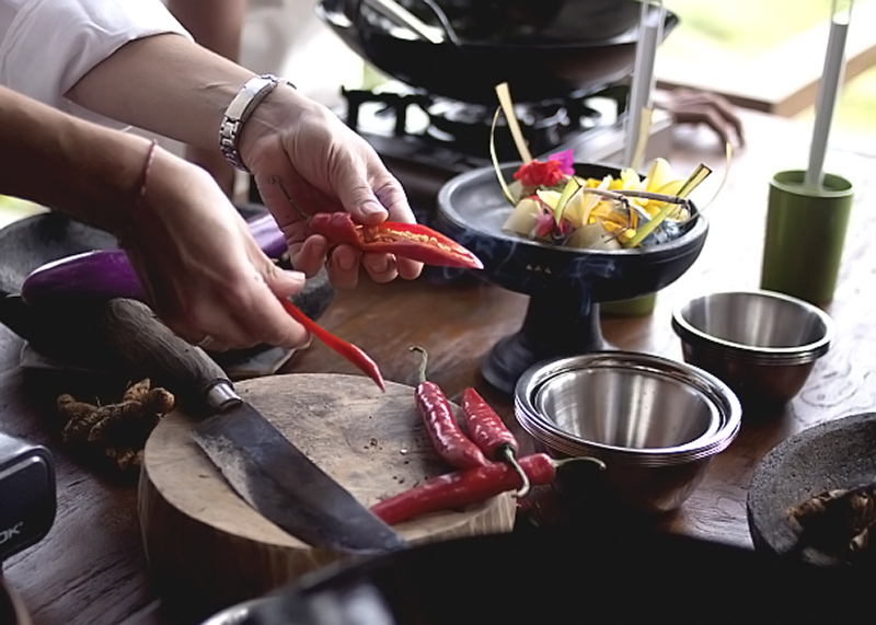 Hands holding a halved red chilli over a circular wooden chopping board and knife and steel bowls by them.