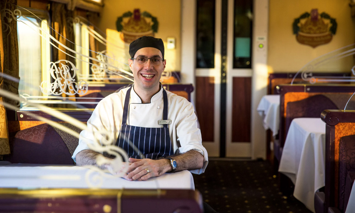 Chef de partie Joe Cobiac sitting in his chef's uniform at a table in the Queen Adelaide restaurant car.