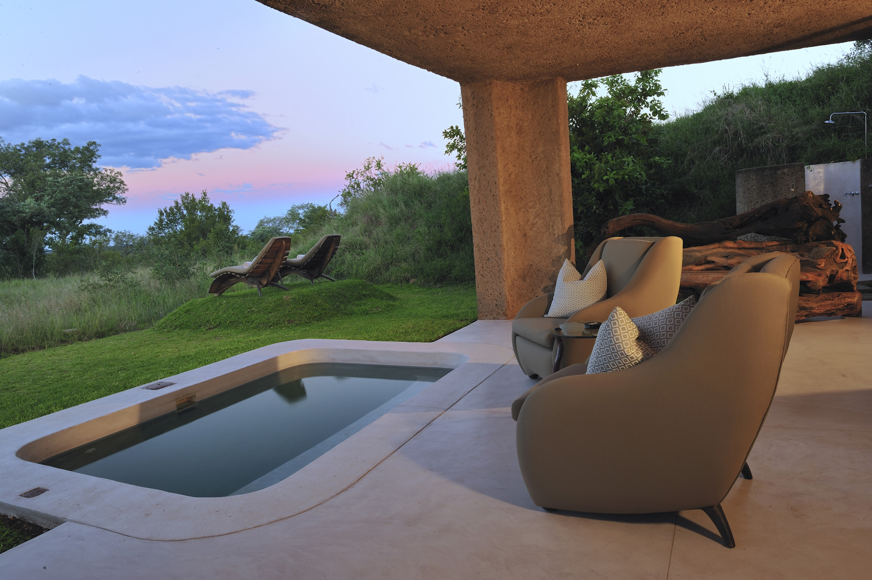 View of a patio, chairs and a plunge pool looking out towards green bush