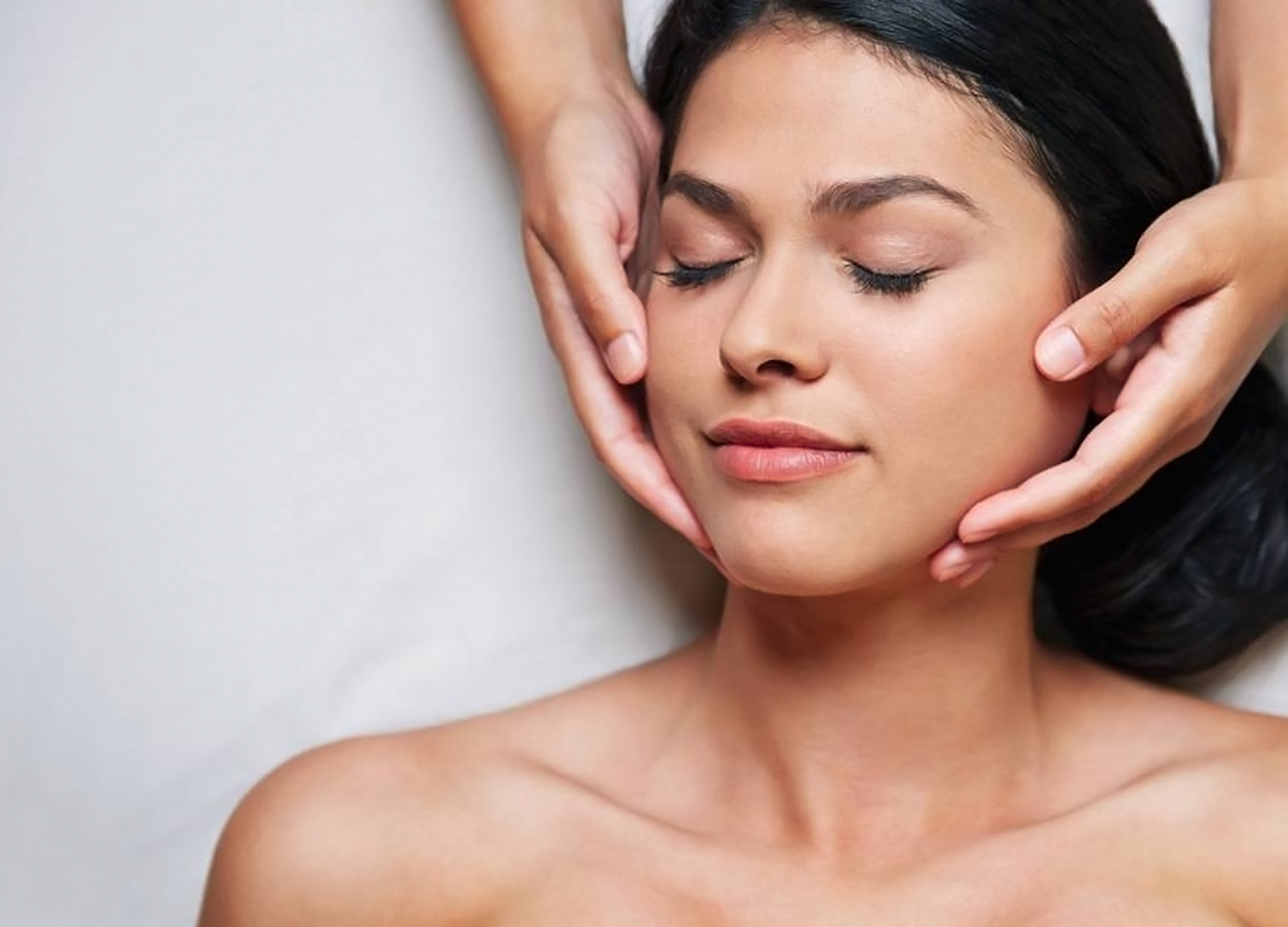 Woman with eyes closed enjoying a facial treatment at the Four Seasons LA spa.