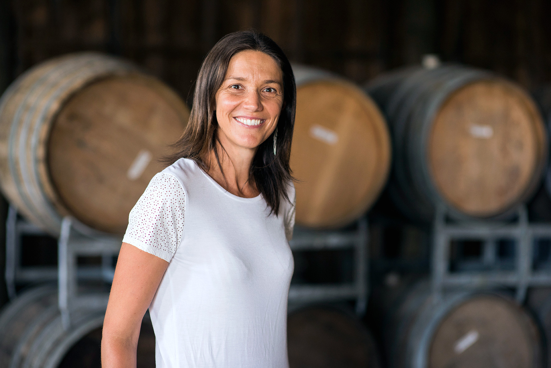 Kirsten Searle, owner of Matawhero Wines posing in front of wine barrels