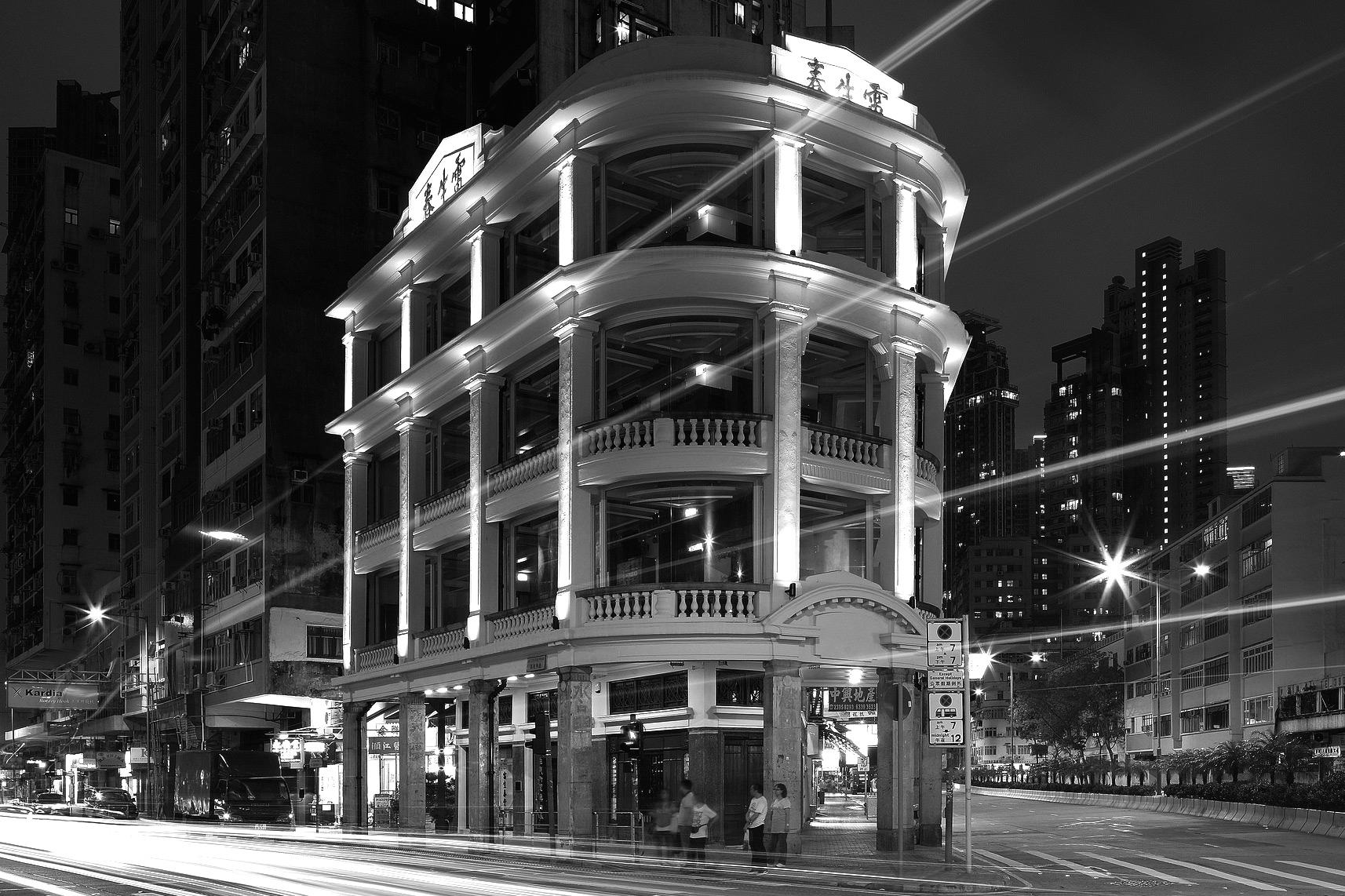 Black and white shot of a corner tenement building, Lui Seng Chun Centre at night in Hong Kong