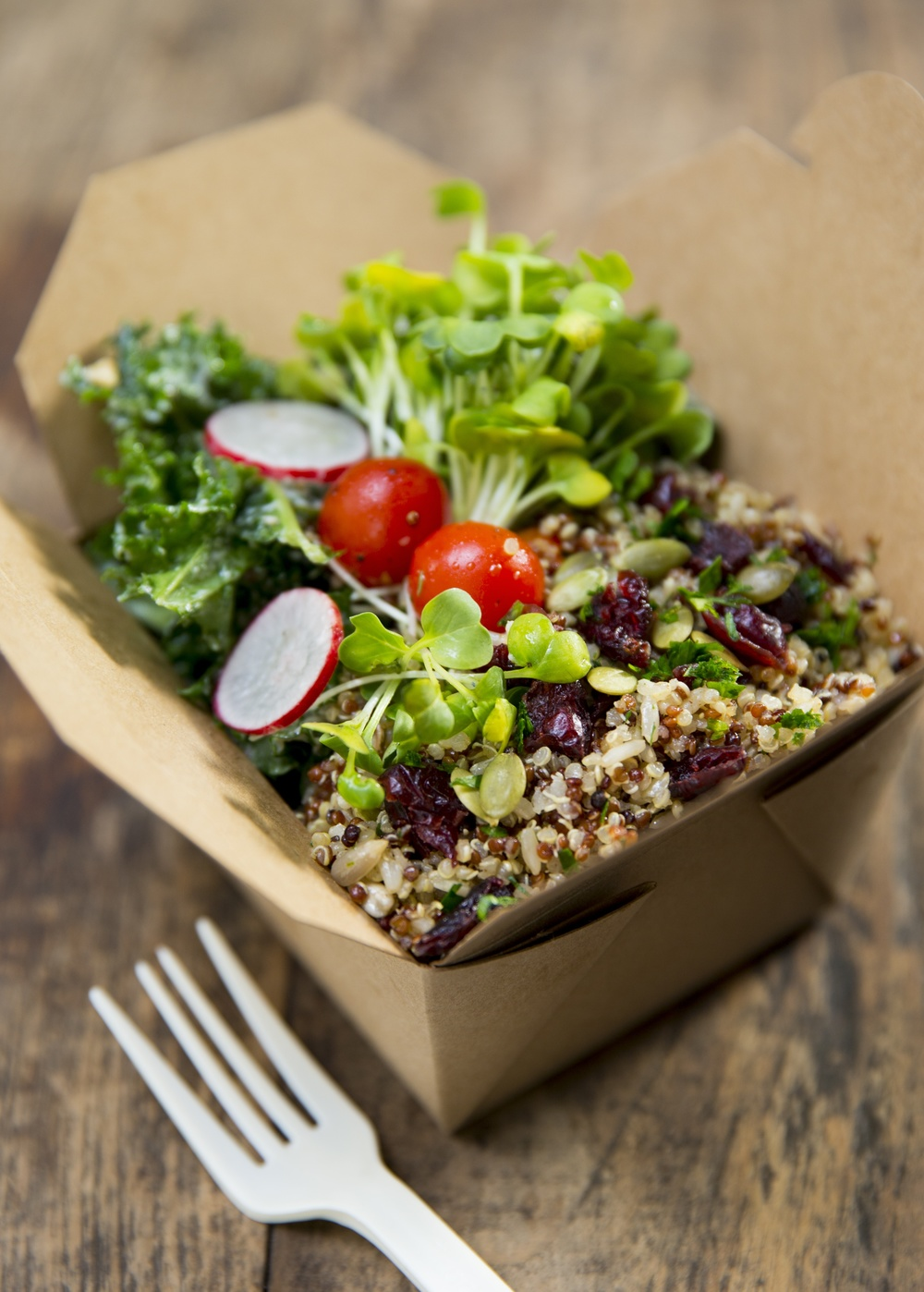Takeaway box of cooked quinoa and rice topped with fresh vegetables and tomatoes at Mana! Fast Slow Food