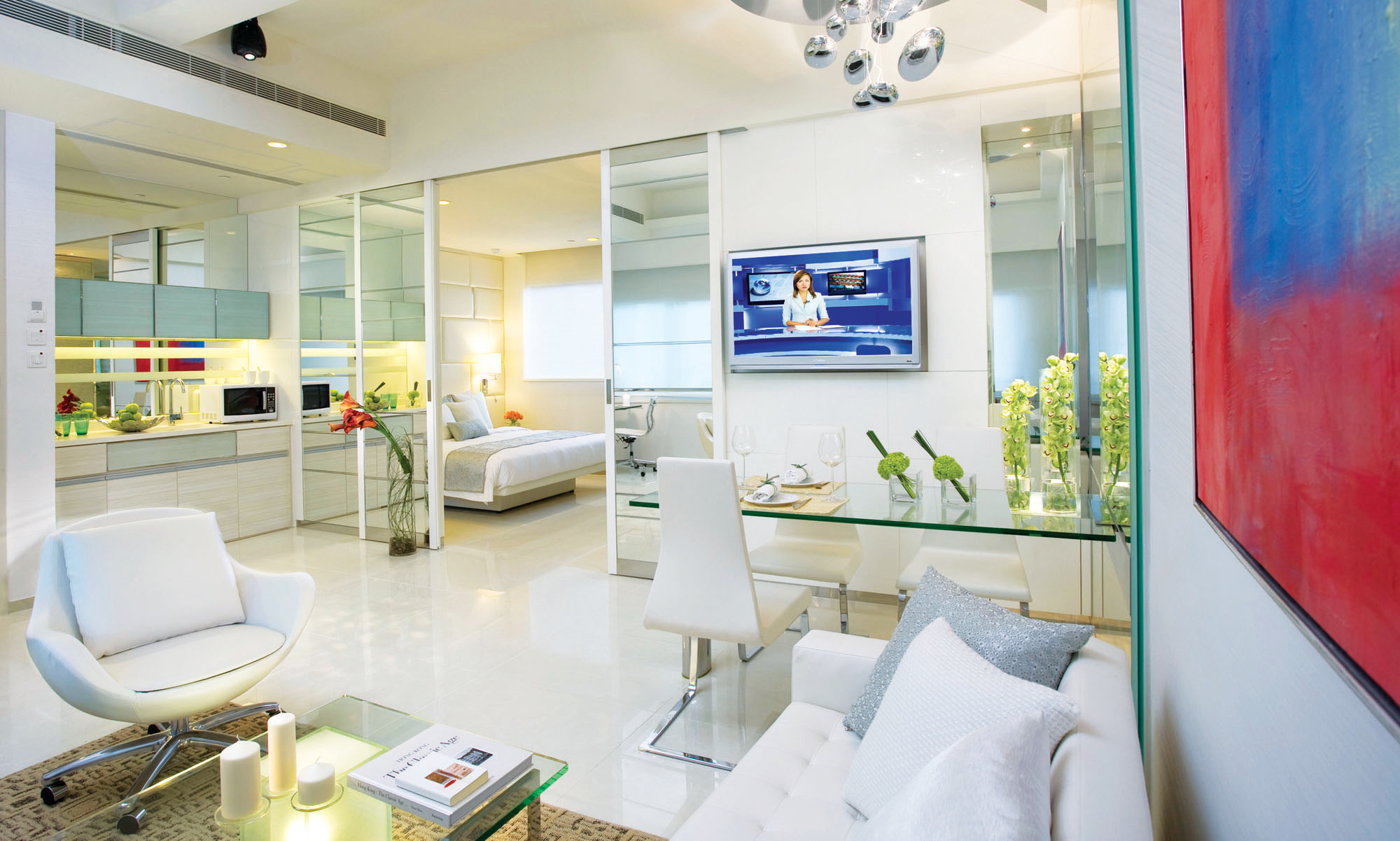 Room with glass partitions and tables with white leather furniture at an I-Suite, Hong Kong