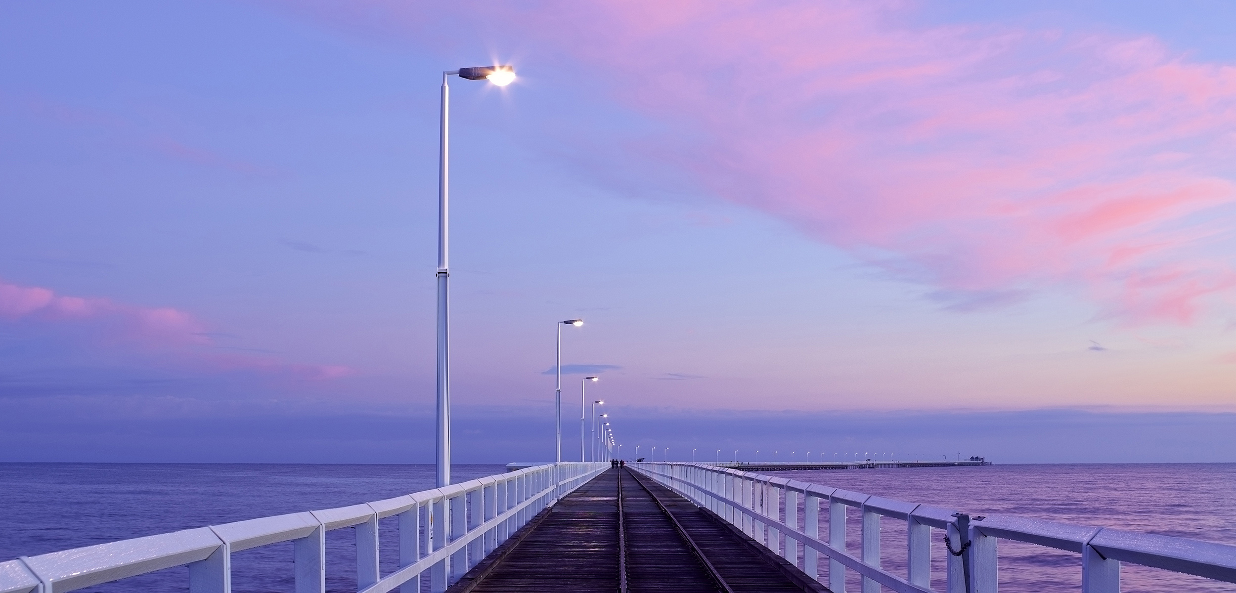 The long wooden Busselton Jetty stretches into the distance with its lampoles lighted up, Geographe Bay in Australia