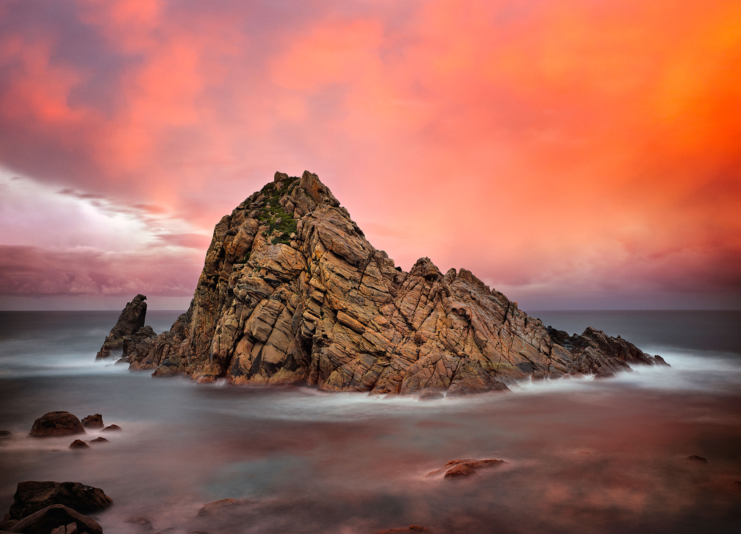 Sugarloaf Rock in the sea with an orange sunset behind it