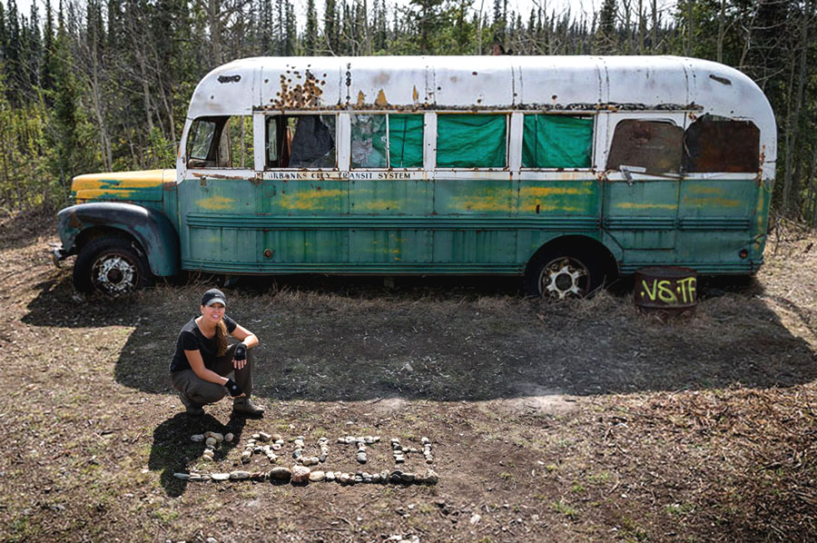 Carine McCandless squatting by a derelict bus with the word truth spelt out in stones by her