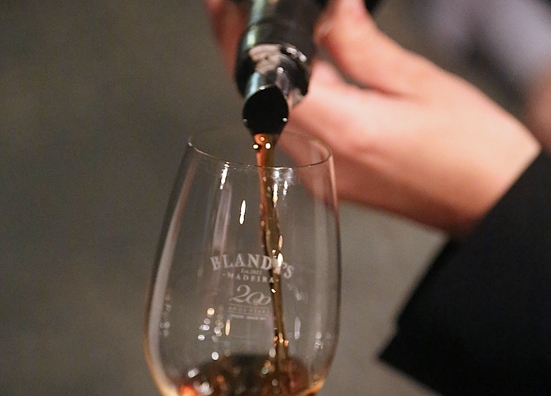 Pouring Blandy's Bual 1969 wine into a monogrammed wineglass