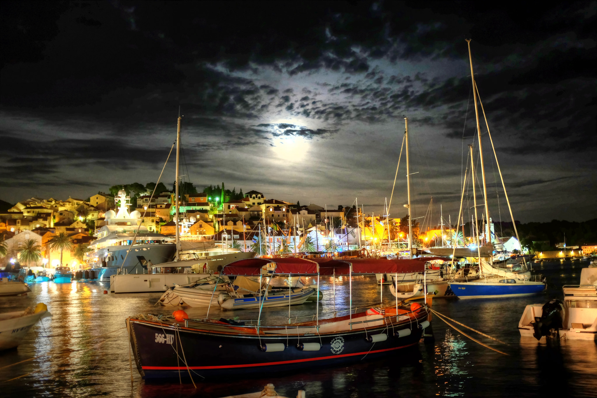 View across boats on the sea to Hvar illuminated by the moonlight and city lights
