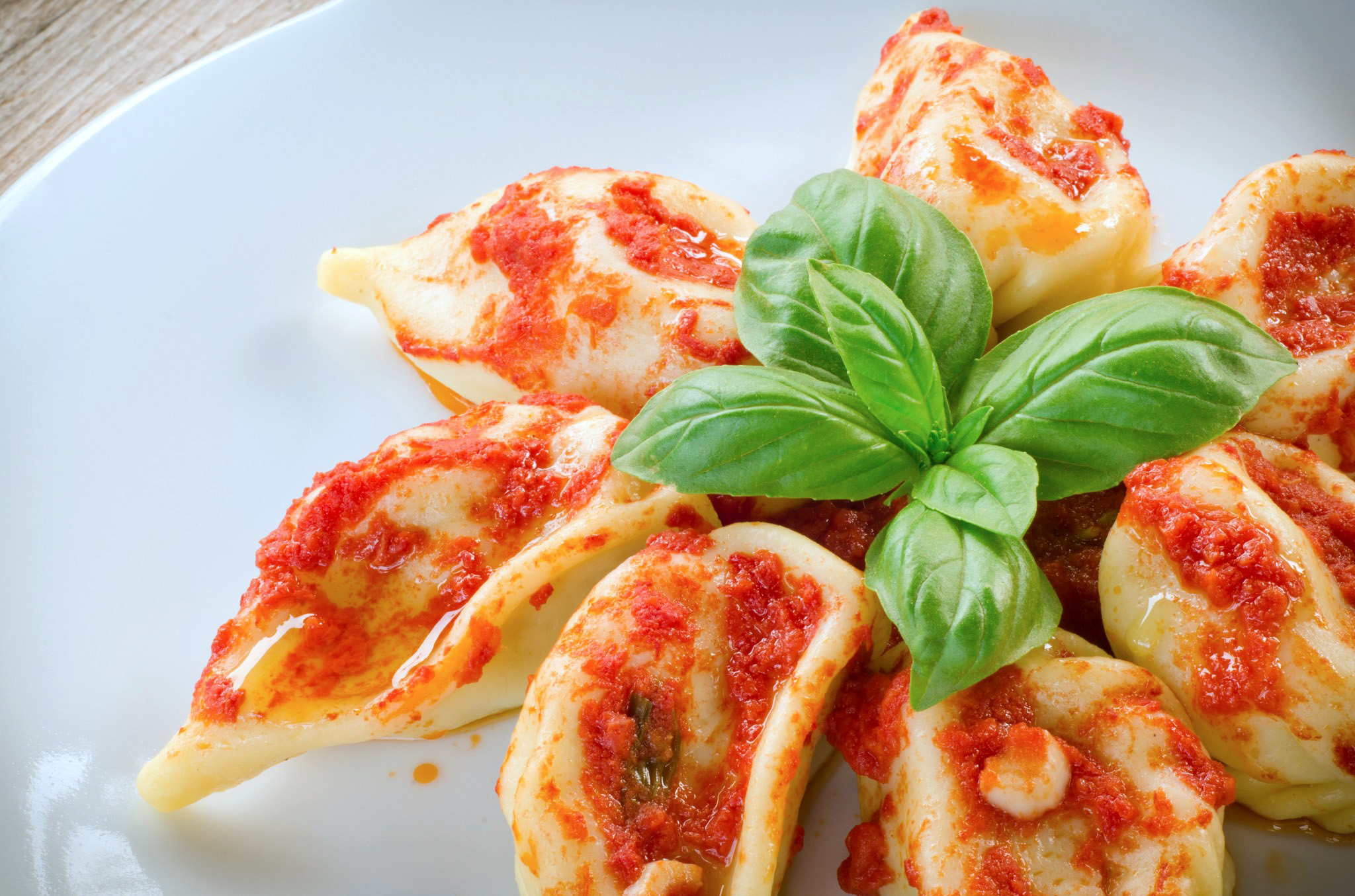 A plate of culurgiones flecked with tomato based sauce, grated pecorino and garnished with a sprig of basil,
