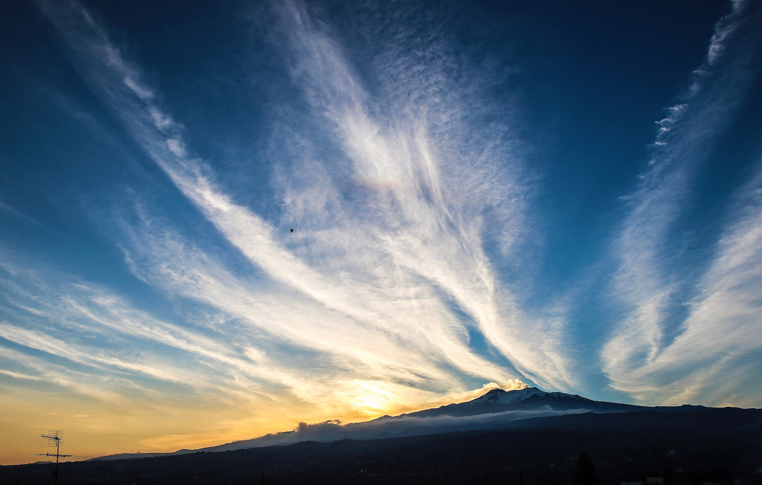 Mount Etna with the sun setting behind it in Sicily, Italy