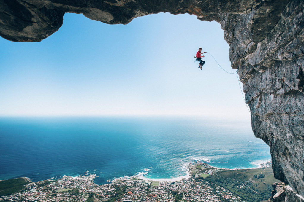 """Cape Town, South Africa Photographing a climber can be difficult. Climbers prefer the shade,  as cooler temperatures provide more friction between skin and rock, but cameras don't, as shade can lead to overexposed backgrounds and underexposed foregrounds. That, coupled with the fact that the best climbing shots often require some form of rigging, means getting a shot like this one is a little out of a regular photographer's comfort zone.   """"We had planned to grab some cool climbing shots but in the end, this image of Jimbo mid-air was the shot we felt captured the intensity of the climb.""""  Category Winner: Wings Photographer: Micky Wiswedel Camera: Canon EOS 5D Mark III"""