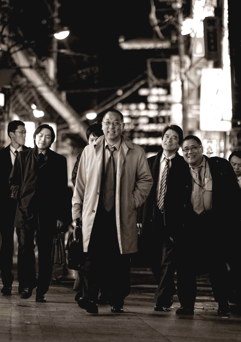A group of Japanese businessmen sauntering down the streets of Tokyo