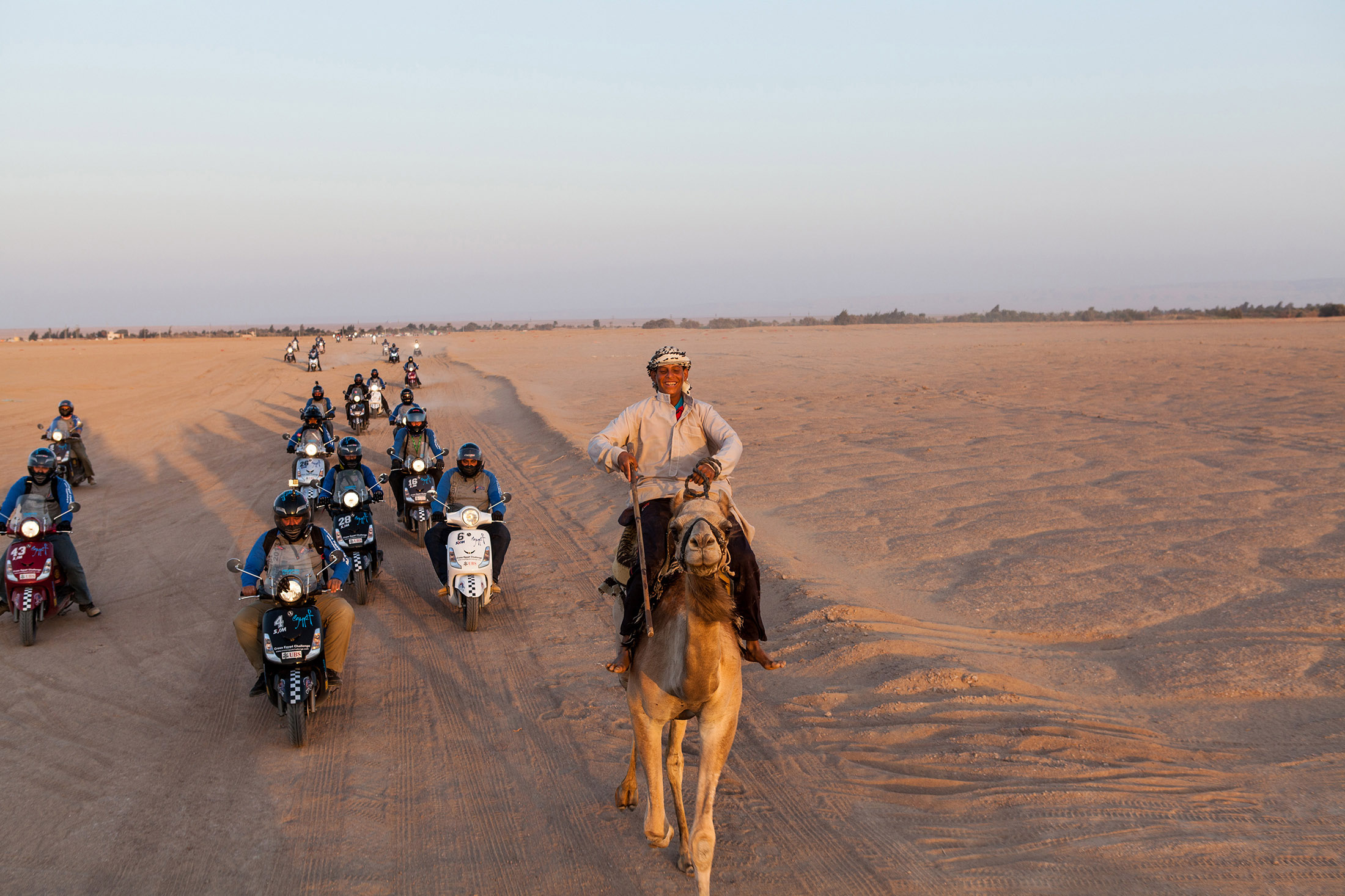 Rider on a camel leading a group of motorcyclists in the desert, Egypt