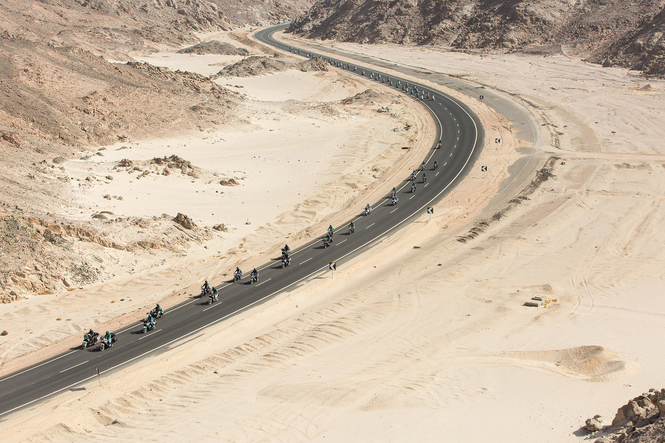 Aerial view of motorcyclists on an asphalt road in the desert on the Cross Egypt Challenge