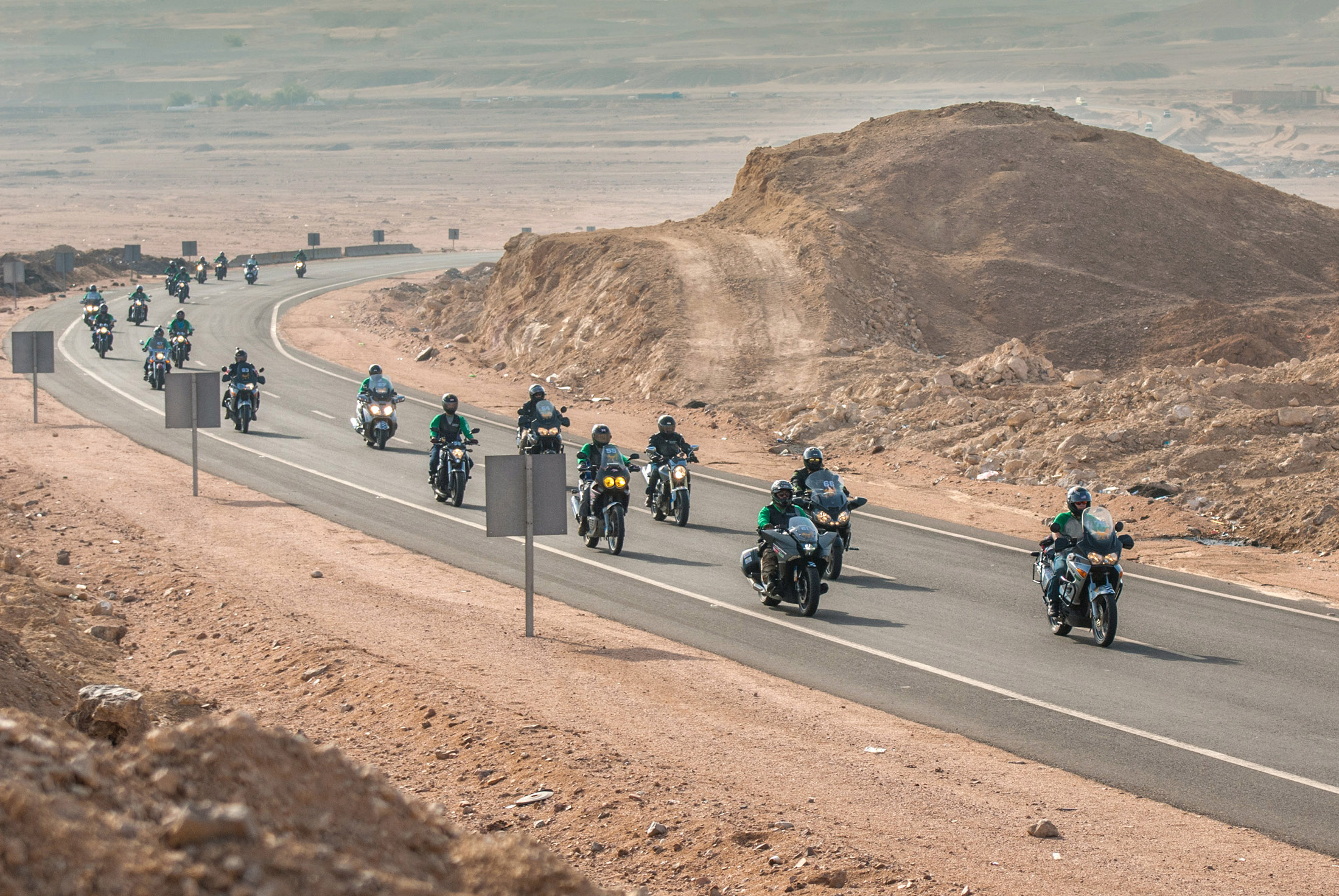 Motorcyclist group rounding a bend on the Cross Egypt Challenge
