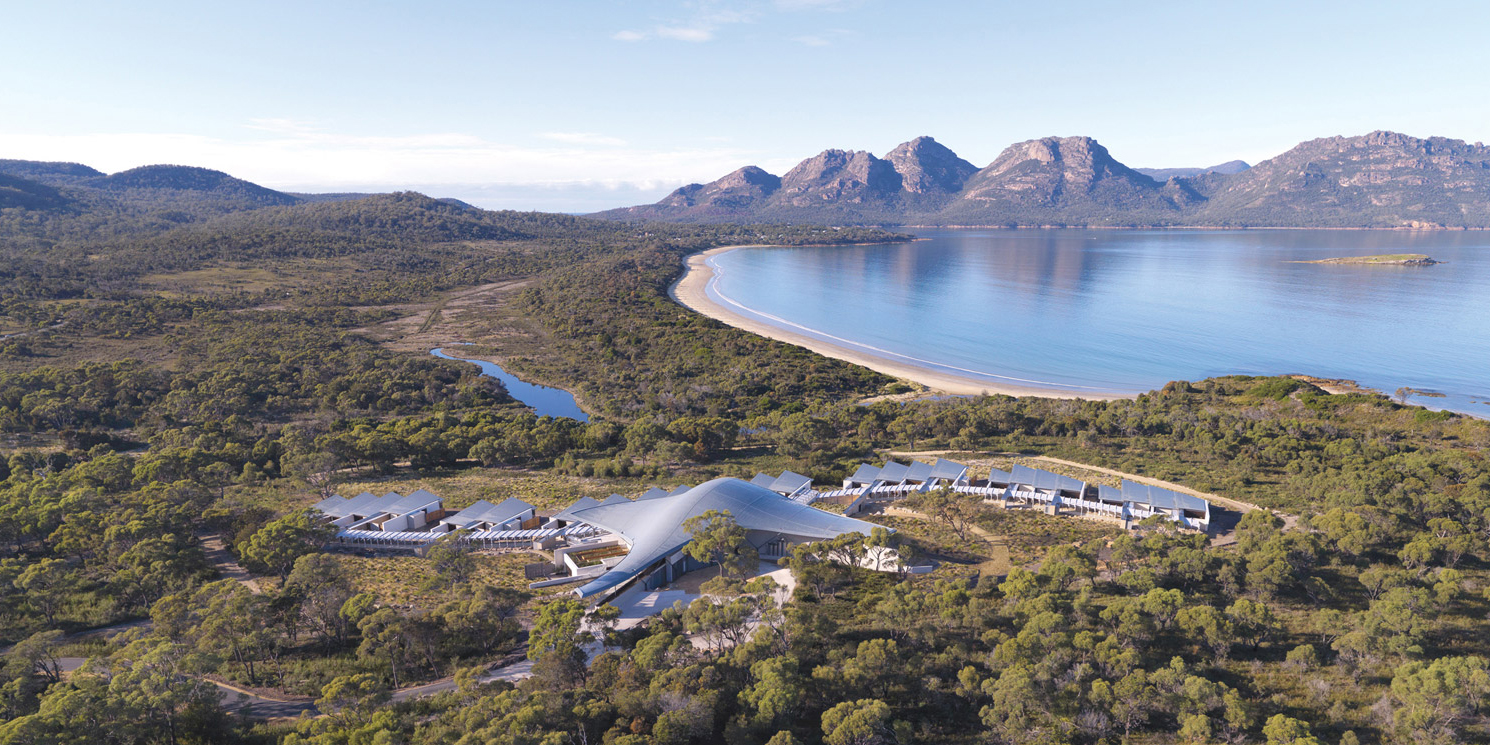 Aerial view of Saffire-Freycinet nestled in the green bush with sea beyond it, Tasmania, Australia