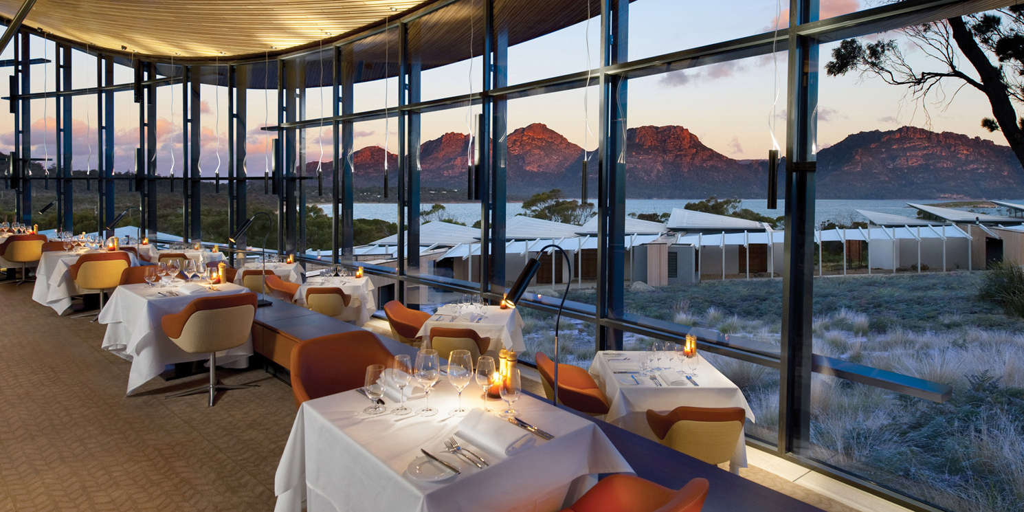 Tables with candles laid for dinner down a long glass window, Palate restaurant at Saffire Freycinet, Tasmania, Australia