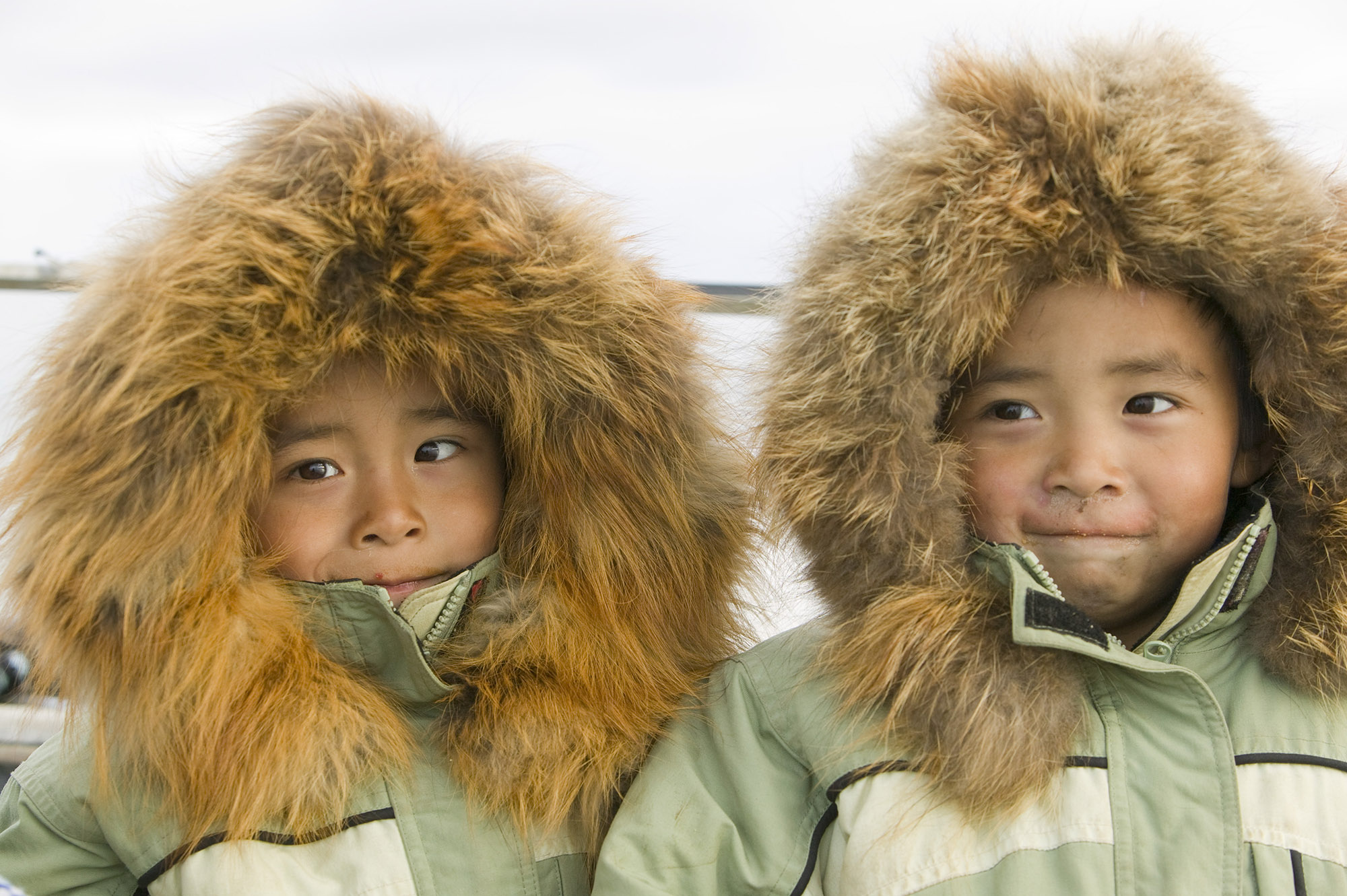 Twin Inuit boys around 7 years old in matching green coats with orange furry hoods