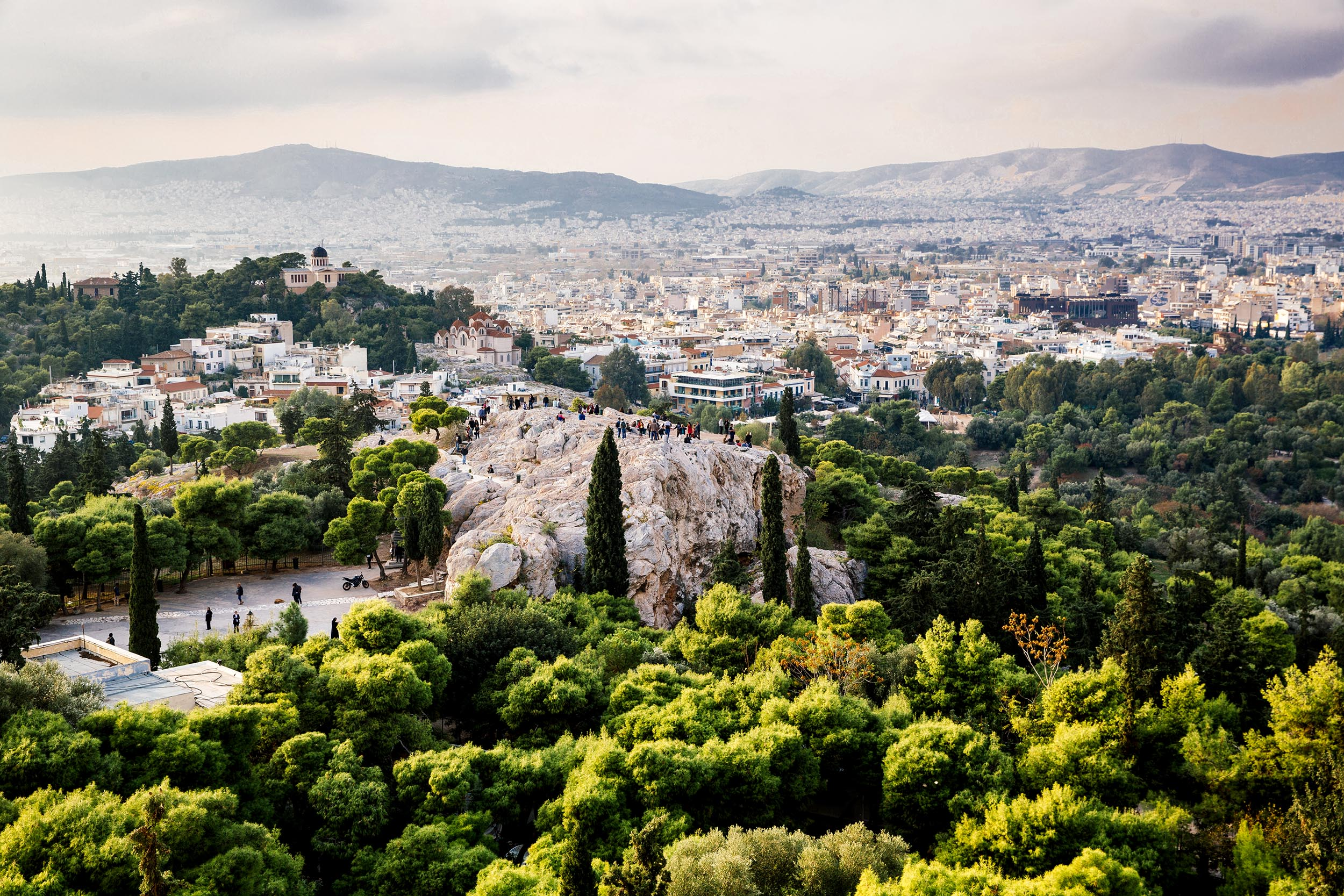 View out to rocky outcrops with people on them, and the city of Athens to the hills in the distance at evening time