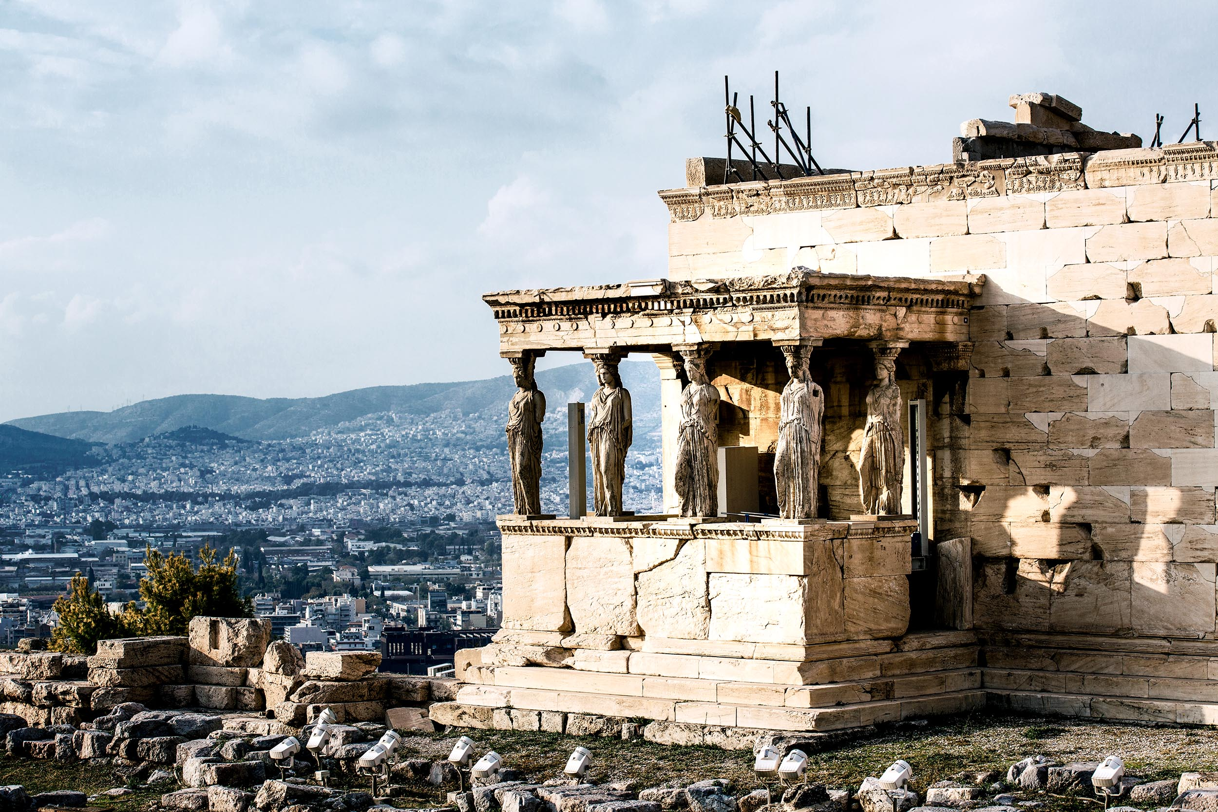 Six female statues supporting the roof of a porch at the crumbling Erechtheion temple, Athens