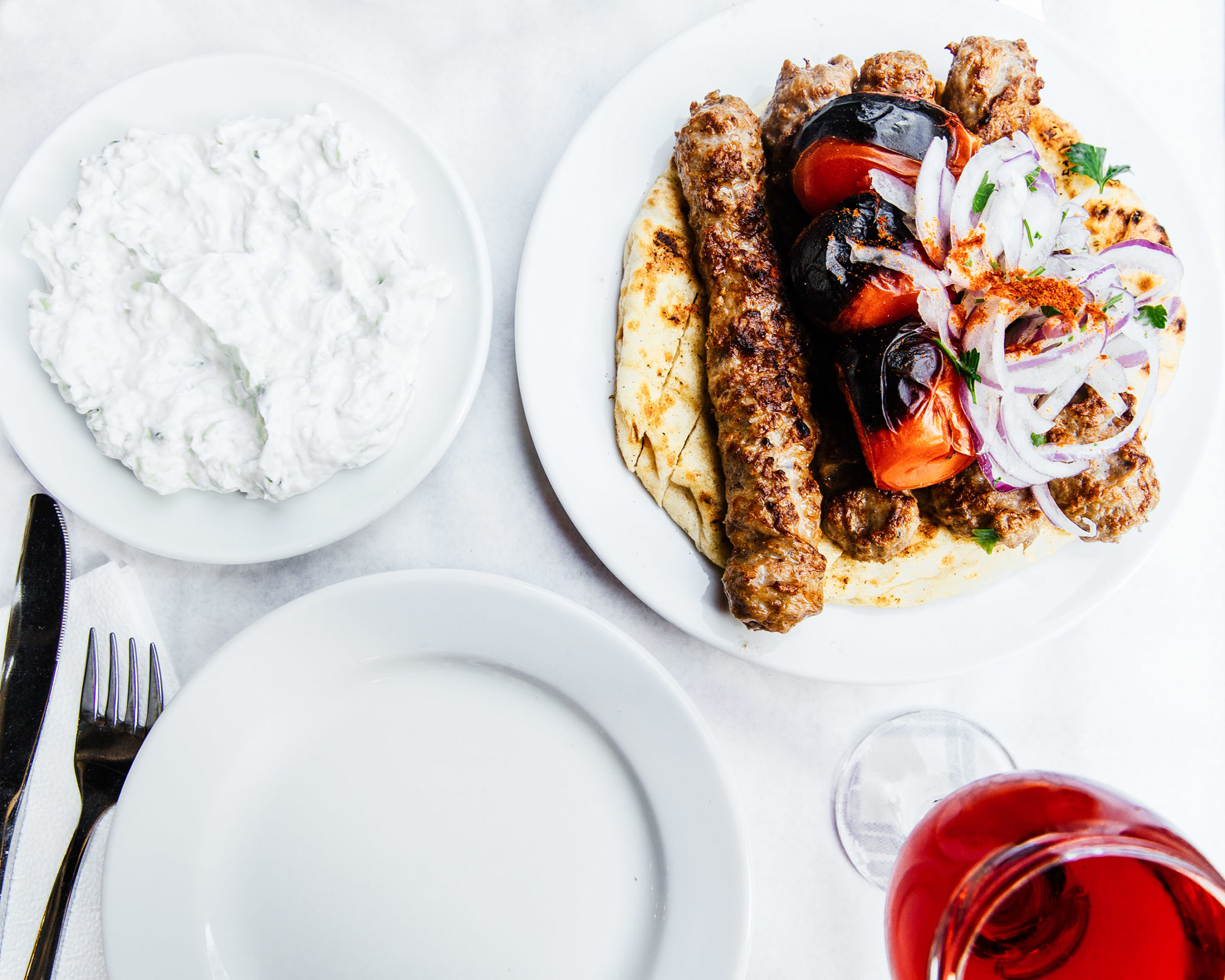 A plate of gyros by some tzatziki in another plate and a glass of wine