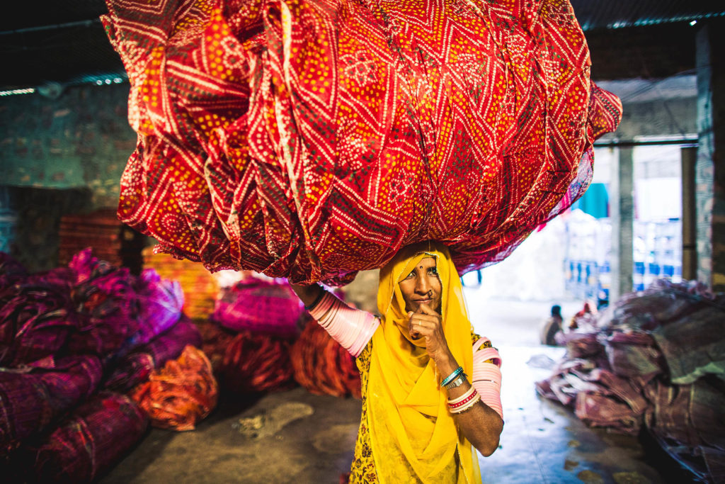 An Indian woman carries a heavy load on her head as part of her daily routine in Jodhpur, India.