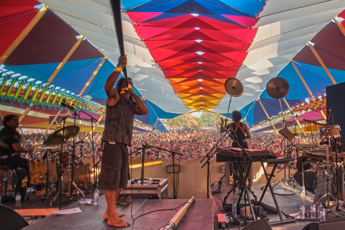 Band playing under a multicoloured tent roof to a large crowd, Portugal
