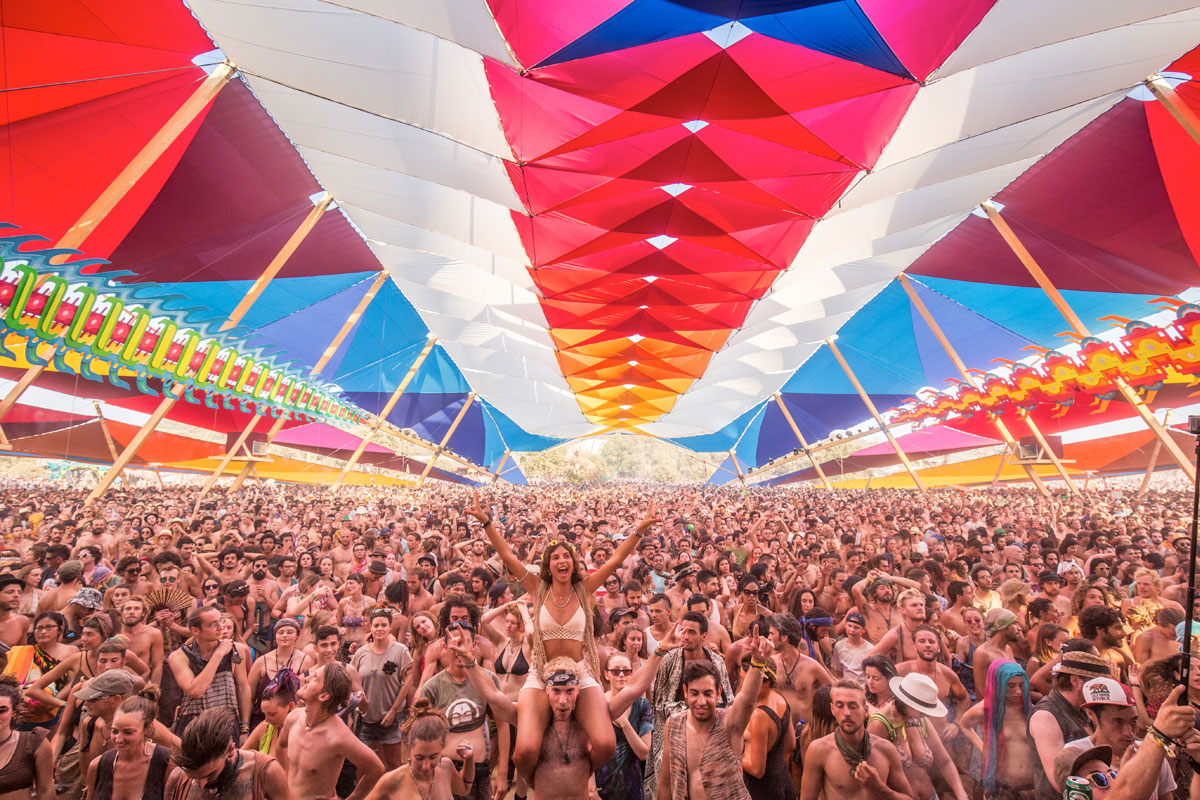 Multicoloured tent over a massive crowd filling the tent up and dancing at Boom Festival