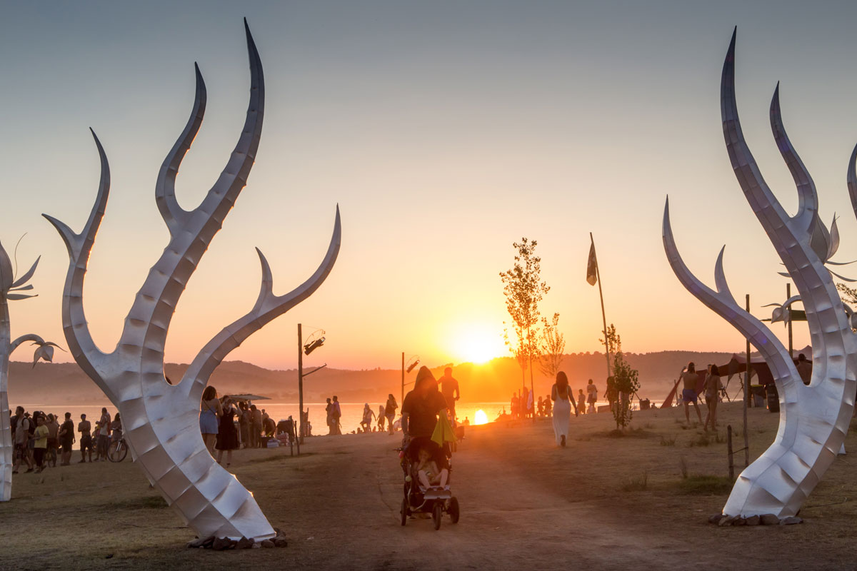 Antler-like installations by Idanha-a-Nova Lake with a father pushing his son in a pram through them at sunset