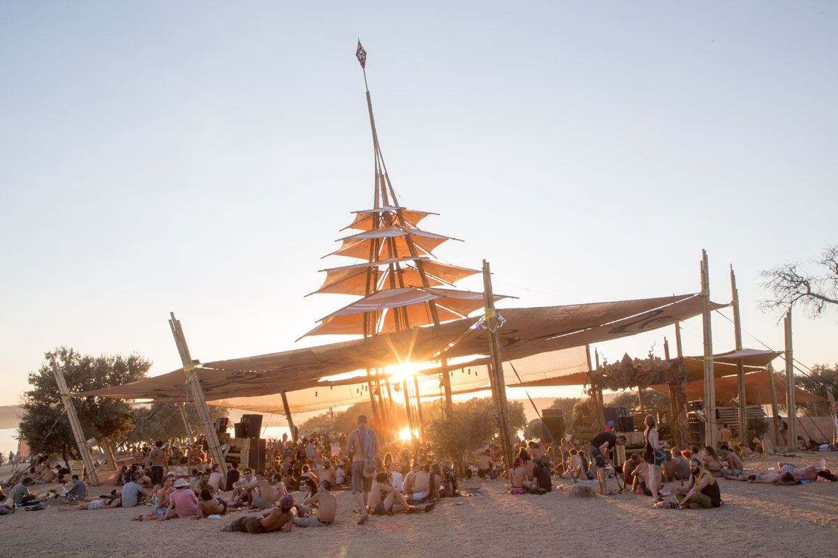 Crowd sitting under an open-sided tent by the lake at sunset