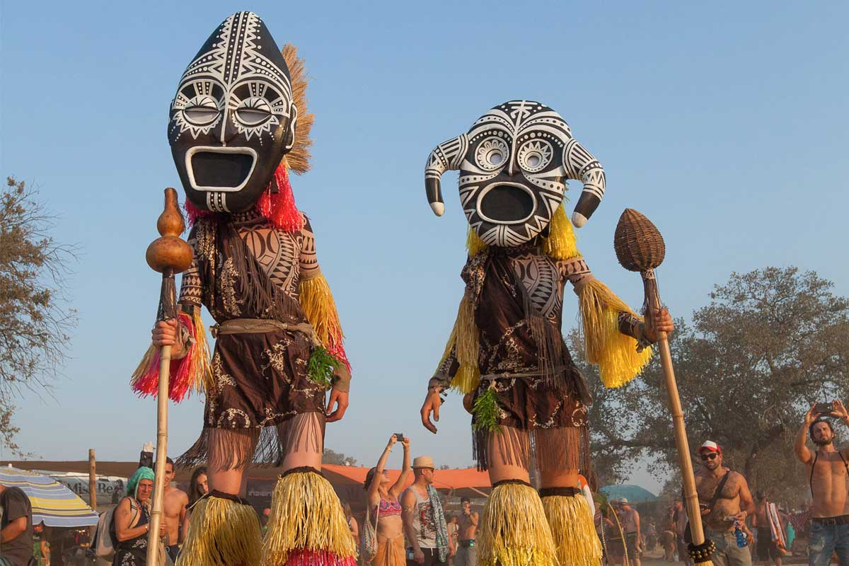 Two tall figures on stilts with masks on at Boomland