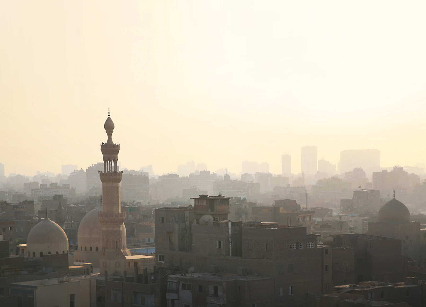 View over a foggy Cairo city with a mosque's domes and minaret in the foreground