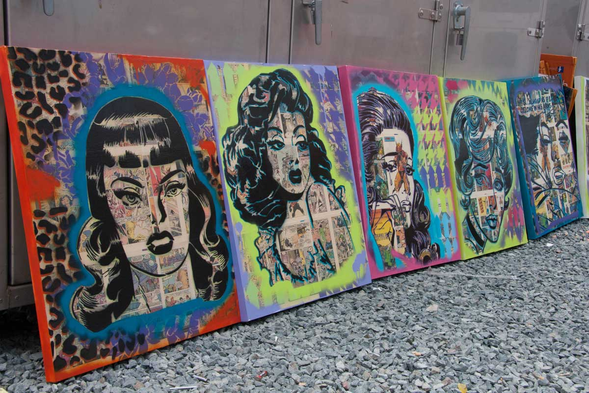 Artwork of comic book heroines faces lined up against a wall at Comic-Con, San Diego