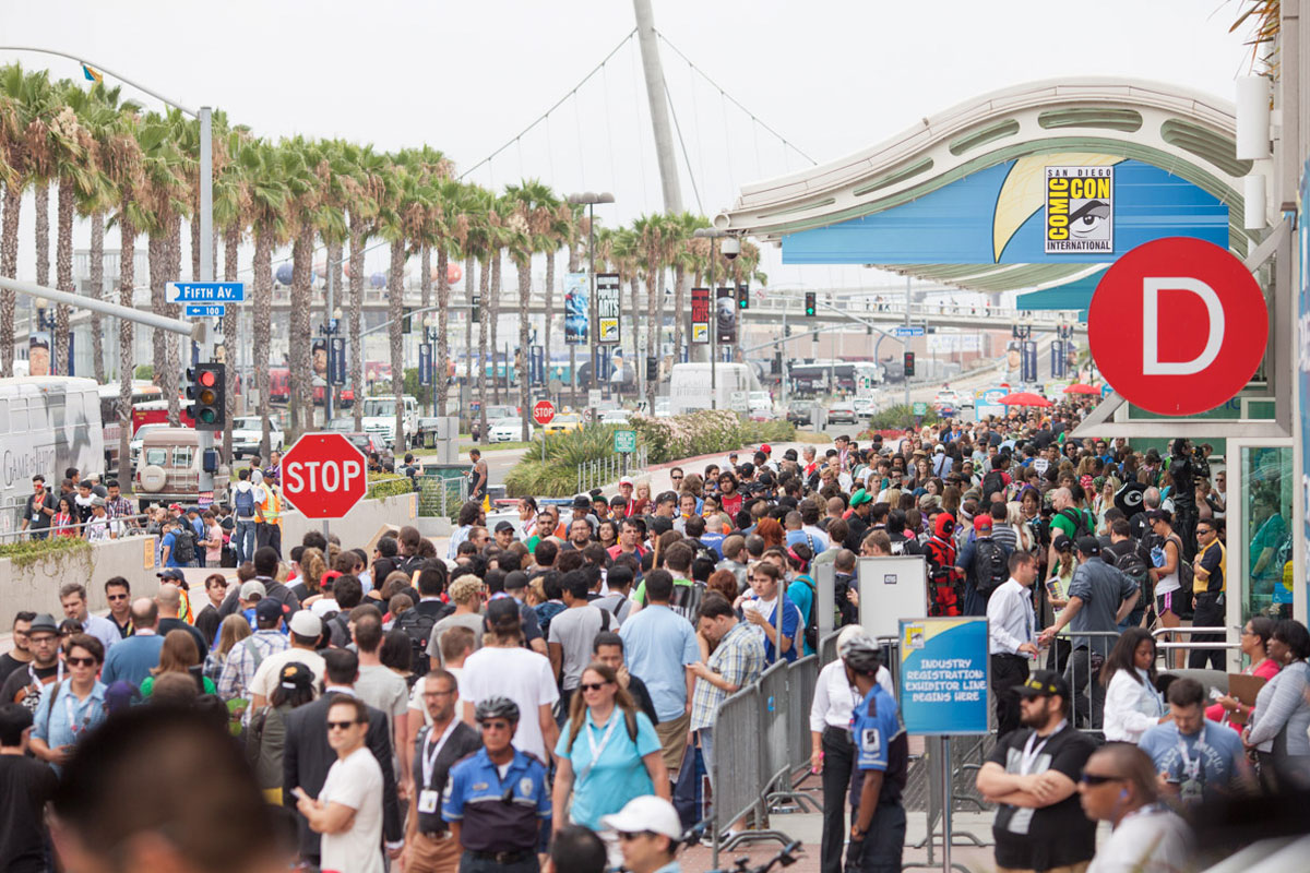Crowd walking outside Comic-Con convention centre with a palm tree lined boulevard behind it, San Diego