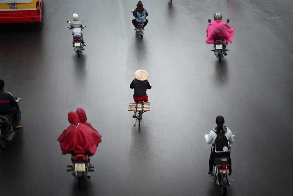 A busy street scene in Hanoi on a rainy morning.