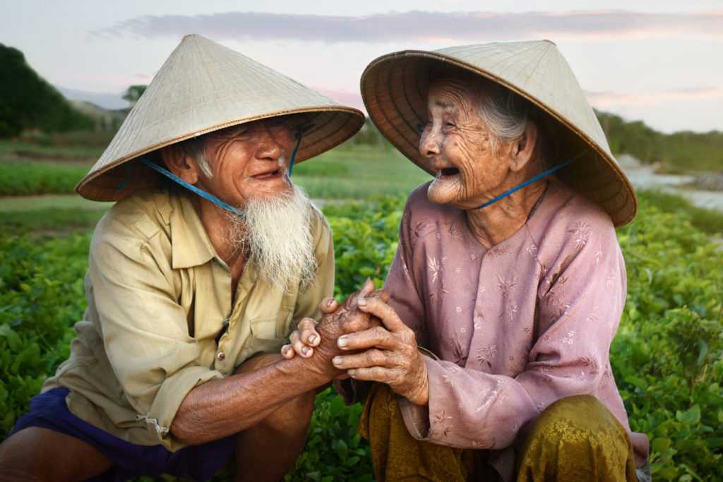 A loving couple in Hoi An share a moment of joy and happiness together in their garden as the sun sets. At the time of photography, they have been married for 66 years.