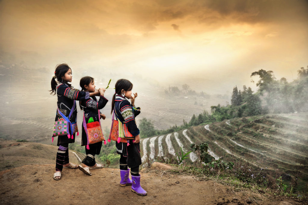 Three village girls from a hill tribe in Sapa look out over their world of mountains and rice terraces.