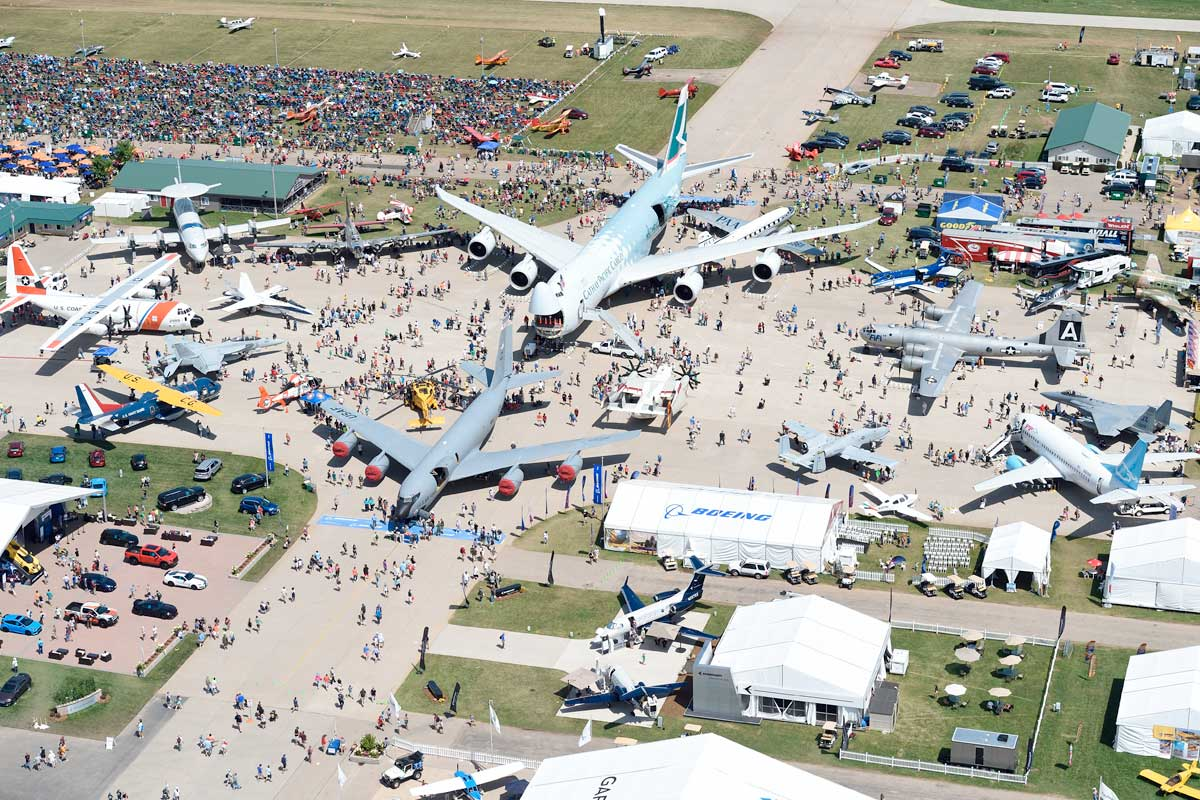 Aerial view of the tarmac and multiple aircrafts parked and visitors at EAA AirVenture, Oshkosh