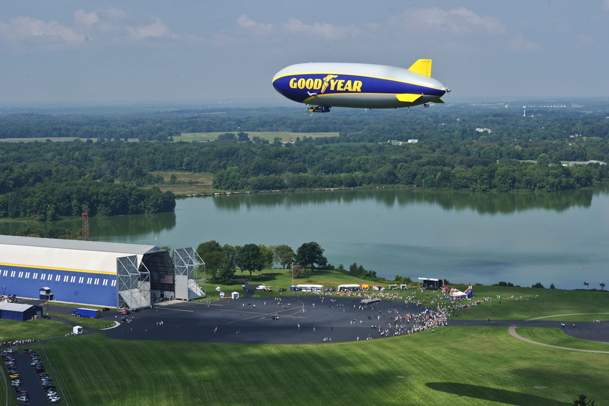 An airship flying over the show-grounds and crowd