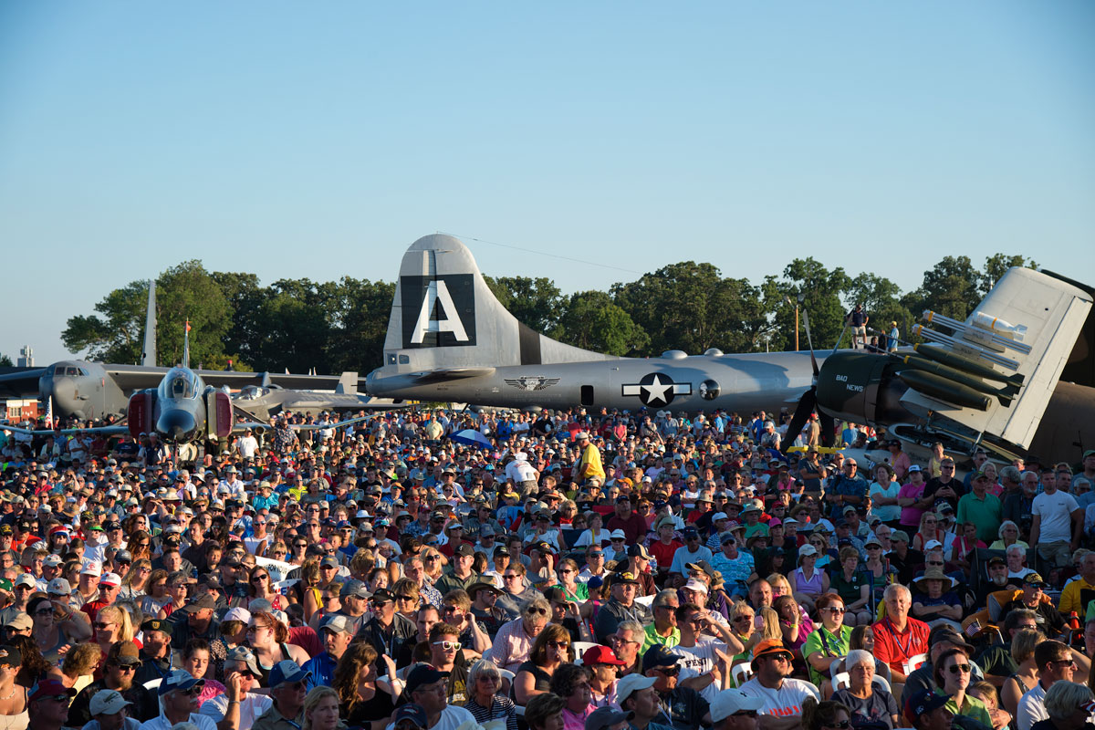 Crowd seated on chairs amongst the planes watching a show at EAA AirVenture, Wisconsin